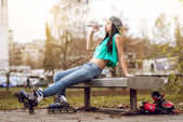 Roller girl drinking water on bench — Stock Photo