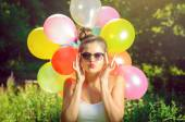 Girl posing with balloons in nature — Stock Photo