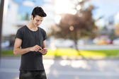 Happy young man writing message on mobile phone — Fotografia Stock