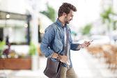 Jonge man met behulp van mobiele telefoon in street — Stockfoto