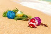 Christmas balls with fir twig on sand — Stock Photo