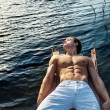 Muscular man lying on wooden jetty — Stock Photo #73262813