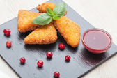 Fried cheese sticks served with cranberries, sauce on black ston — Stock Photo