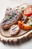 Portion of BBQ t-bone steak with  sauce  and grilled vegetables — Stock Photo