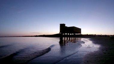 Západ slunce a historické plavčík budova v popředí, na fuseta rybářské městečko, ria formosa památkově chráněný park, algarve. Portugalsko — Stock video