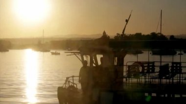 Boats silhouette at sunset, in Quatro Aguas fishing port background, view from Tavira Island, Ria Formosa Natural Reserve. Algarve. — Stock Video