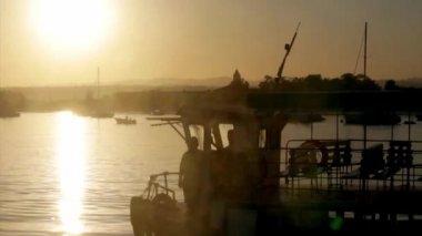 Silueta lodi při západu slunce, Quatro Aguas rybářského přístavu pozadí, pohled z ostrova Tavira, přírodní rezervaci Ria Formosa. Algarve. — Stock video