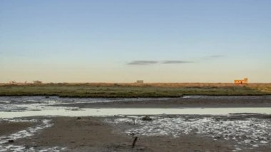 Moonrise Time lapse, at Ria Formosa wetlands natural park landscape, view from Fuzeta town to historic life guard building and also some crabs moving in foreground — Stock Video