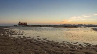 Sunset and historic life-guard building in the foreground, at Fuseta fishing town, Ria Formosa conservation park, Algarve. — Stock Video
