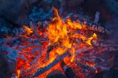 Campfire in rock fire ring at dusk — Stock Photo