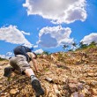 Man climbing up red rock — Stock Photo #70571647