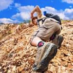 Man climbing up red rock — Stock Photo #70571821