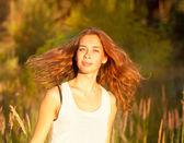 Wunderschöne lächelnde frau in einem feld bei sonnenuntergang mit fliegenden haare — Stockfoto