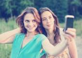 Two beautiful girls make selfie on a mobile phone — Stock Photo