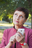 Pensive attractive woman 50 years with mobile phone in hand — Stock Photo