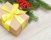 Beige gift box with yellow ribbon on fir branches background — Stock Photo