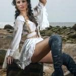 Pirate woman sitting on the beach — Stock Photo #78213922