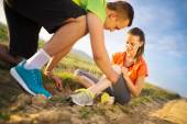 Woman with injured knee getting help — Stock Photo