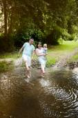 Happy family splashing water in the river — Stock Photo
