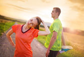 Couple stretching and exercising at sunset — Photo