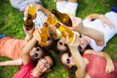 People lying on the grass with drinks — Stock Photo