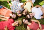 People lying on the grass and taking selfie — Stock Photo
