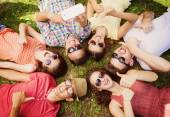 People lying on the grass and taking selfie — Stockfoto