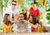 Happy friends in pub garden — ストック写真
