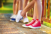 Legs of boys and girls standing on the sidewalk — Stock Photo