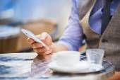 Businessman using mobile phone in cafe — Stock Photo