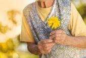 старшие женщины холдинг цветок — Стоковое фото