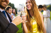 Wedding guests clinking glasses — Stock Photo