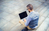 Hipster businessman using laptop on stairs — Stock Photo