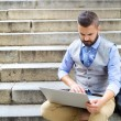 Businessman using laptop in the city — Stock Photo #55291401