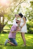 Pregnant family having fun in garden — Stock Photo