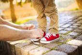 Father's hands tying his son's shoes — Stock Photo