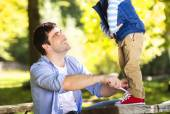 Father is helping his son to tie shoes — Stock Photo