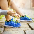 Female athlete tying sport shoes — Stock Photo #55629863