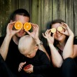Family with little boy having fun with oranges — Stock Photo #56086359