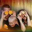 Family with little boy having fun with oranges — Stock Photo #56086373