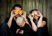 Family with little boy having fun with oranges — Stock Photo