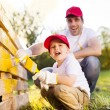 Father with son painting wooden fence — Stock Photo #56178483