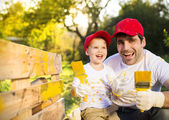 Father with son painting wooden fence — Stock Photo