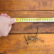 Hand measuring flooring with tape measure — Stock Photo #56188167