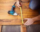 Hands measuring flooring with tape measure — Stock Photo