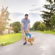 Father pushing his son in wooden wheelbarrow — Stock Photo #56452769