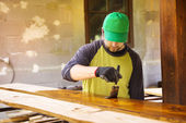 Handyman varnishing pine wooden planks — Стоковое фото