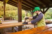 Handyman varnishing pine wooden planks — Stockfoto