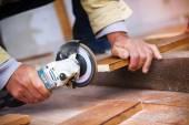 Hands grinding wooden planks — Stock Photo