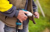 Handyman holding drilling machine — Stock Photo